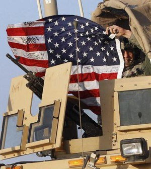 A U.S. Army soldier waves an American flag after crossing into Kuwait during the last convoy out of Iraq